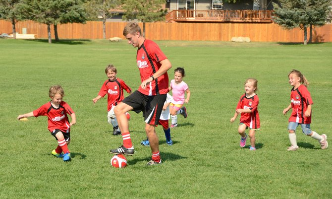 Ashley Clamp of Northamphton, England, dribbles away from his three to five year old campers as they give chase to try and steal the ball. Clamp was one of three instructors from England leading the British Soccer Camp from Challenger Sports at Woodbury Sports Complex this week.
