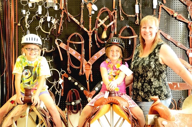 Madison Hadley, left, and her sister Ashlie sit on horse saddles next to their mother, RaeAnne Hadley, who owns a new store called Northwestern Tack. The store opened in May and caters to the equine lovers in the area.