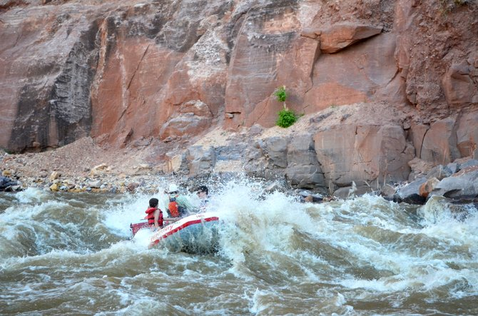 A raft punches through a wave at the top of Warm Springs Rapid in Yampa Canyon on June 9.