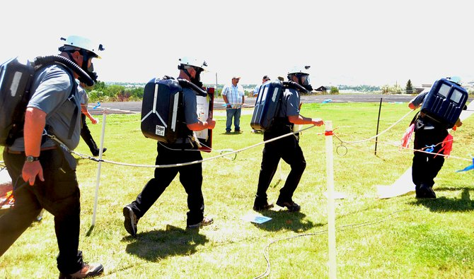 A group of men compete in a mine safety class that was held at Moffat County High School's football field Wednesday.