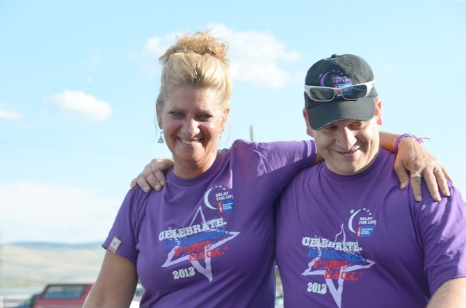 Tamara Piona and Ken Prescott lend each other some support as they finish the survivors lap of Relay For Life on Friday night at the Moffat County Fairgrounds. The annual event is a community fundraiser for cancer research and a tribute to those affected by the disease.