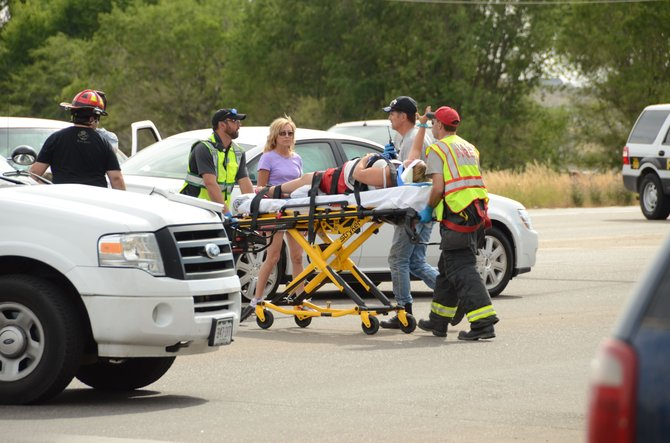 Emergency responders assist an unidentified crash victim Tuesday afternoon. Two cars collided on US Highway 40 in front of Walmart. The six people involved, four adults and two small children, were not critically injured but were taken to The Memorial Hospital.