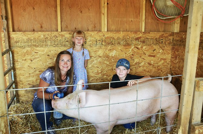 Chris, Jolene, 6, and Pepper Rhyne, 8, hang out with their pig Snow. Pepper has been prepping Snow for the Moffat County Fair that will take place at the fairgrounds in Craig Aug. 5 through 10.
