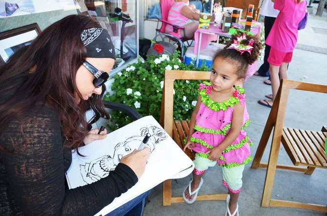 Amanda Field draws a caricature of Alexa Hayden, 3, at Do It Downtown Thursday on Yampa Avenue — an event that takes place every Thursday from 4 to 7 p.m. in downtown Craig. Field charges $5 per caricature. She also does face painting.