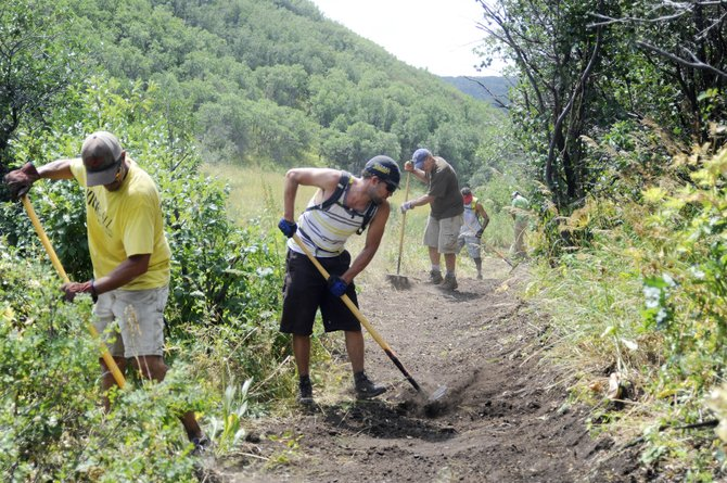 Volunteers, from front, Bill Murphy, Nate Vacura and Mark Simril, work to widen the Ridge Trail on Saturday to make it accessible to hand cyclists who want to ride the connecting Rotary Trail.