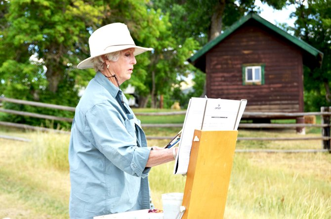 Barbara Wilaby begins the painting process on the edge of an overlook at Ida Gordon's ranch south of Hamilton. Wilaby was one of numerous Moffat County women who gathered at the spot Wednesday afternoon to create art and socialize.