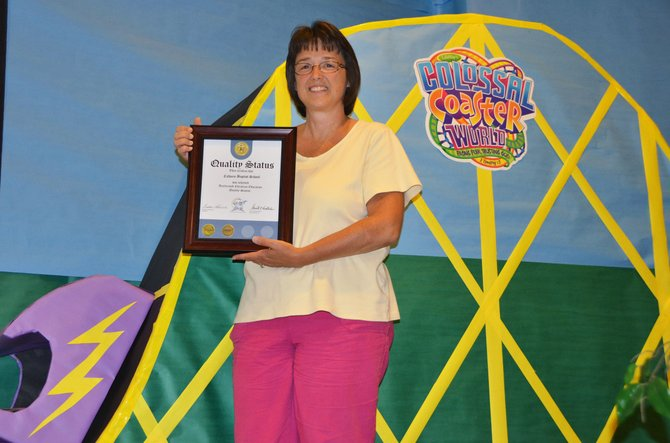 Jamie Tipton holds high the latest honor for Calvary Baptist School amid the amusement park-themed Vacation Bible School at Calvary Baptist Church. The private school is entering its fourth year in Craig and recently received acknowledgement form the Accelerated Christian Education program for the second year in a row.