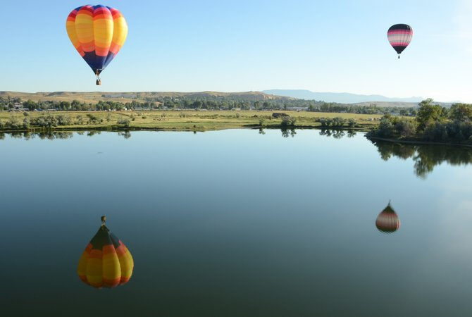 Two balloons fly over a lake north of Loudy-Simpson Park on Saturday morning. The 2013 Moffat County Hot Air Balloon Festival began with 15 balloons launching from Loudy-Simpson. It continues throughout the day and will feature another launch Sunday morning.