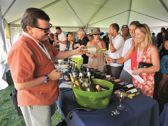 David Walden, district manager for Heck Estates, pours a glass of wine for Erin Dickerson during the 2012 Steamboat Wine Festival tasting in downtown Steamboat Springs. The Steamboat Wine Festival is celebrating its 10th anniversary this week, and its continued popularity has led to the event's expansion into five days this year.