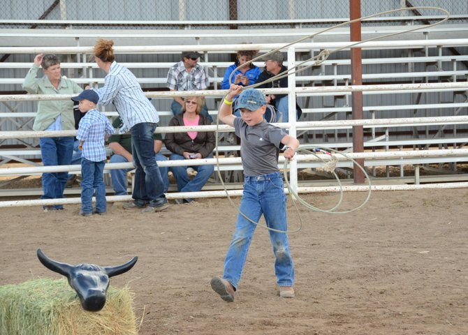 Pepper Rhyne, 8, lassoes a fake head on top of a hay bale Friday night in the Moffat County Fairgrounds arena. Lassoing was one activity of many available during Family Fun Night at the fair, including cake decorating, tire rolling and live music.