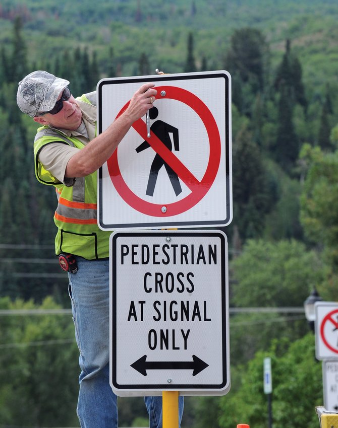 Steamboat Springs employee Dave Burton installs a sign at Sixth Street and Lincoln Avenue on Thursday afternoon. The sign directs pedestrians to cross Lincoln at intersections where a traffic light is present.