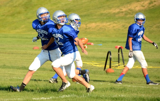 Kearn Gerber (right) and Matt Hamilton (left) look for the ball in a defensive back drill Thursday at Moffat County High School. The Bulldogs football team will finish its first week of two-a-day practices Friday.