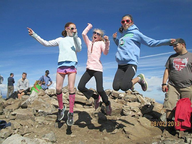 Sarah Meyer, from left, Margaret Dickson and Taylor Olson jumped for joy this month after summiting 14,265-foot Quandary Peak  during a Girls on the Run outing.