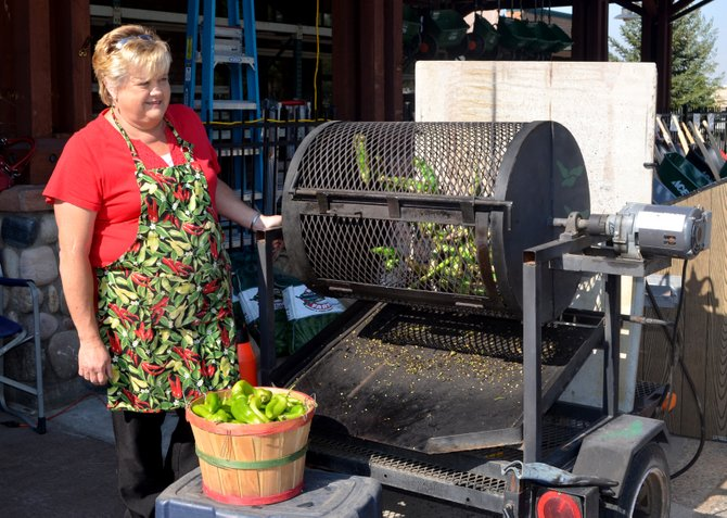 Marilee Figueroa checks on spicy green chiles roasting in a motorized drum fitted with propane burners in front of Ace at the Curve on Friday. Roasting brings out the flavor of the chiles and makes it easy to remove their skins.