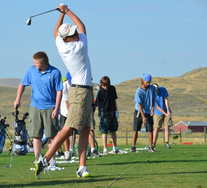 Chris Kling (in white) hits at the driving range at Yampa Valley Golf Course Tuesday morning. Kling and the Bulldogs have posted team scores of 270 in three of four tournaments so far. They now have their longest break of the season to practice before heading to Devils Thumb Golf Course in Delta Aug. 28.