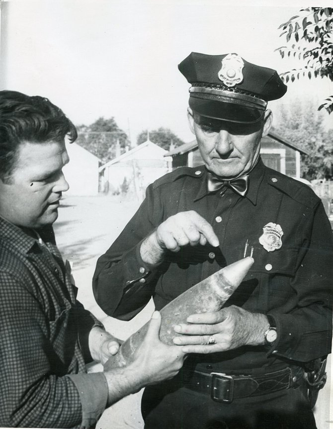 Construction superintendent S.D. Champlin, left, shows City Marshall George Krieger the live tank shell found in 1956 by workmen who were excavating for a curb and gutter paving project at Victory Way and Taylor Street.