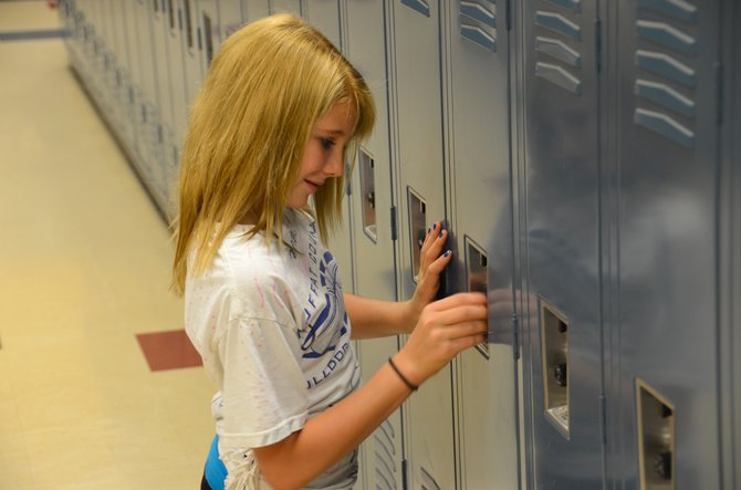Hannah Boulger practices using her locker combination Friday afternoon at Craig Middle School. This is the first year Boulger and other sixth-graders will have a locker as they begin classes at CMS.