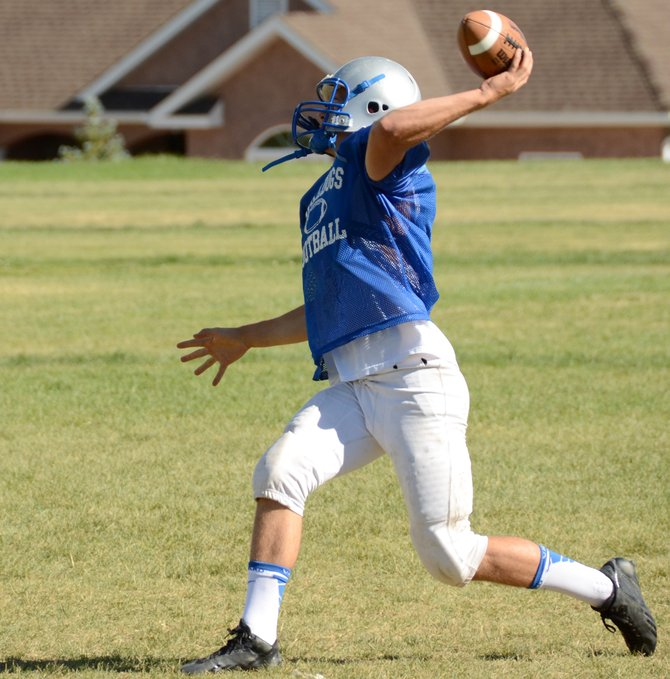 Joe Camilletti throws a pass after rolling out in a drill at Moffat County High School. Camilletti is one of a few returning starters on the offense at wide receiver, and may spend time at quarterback for the Bulldogs this season as well.