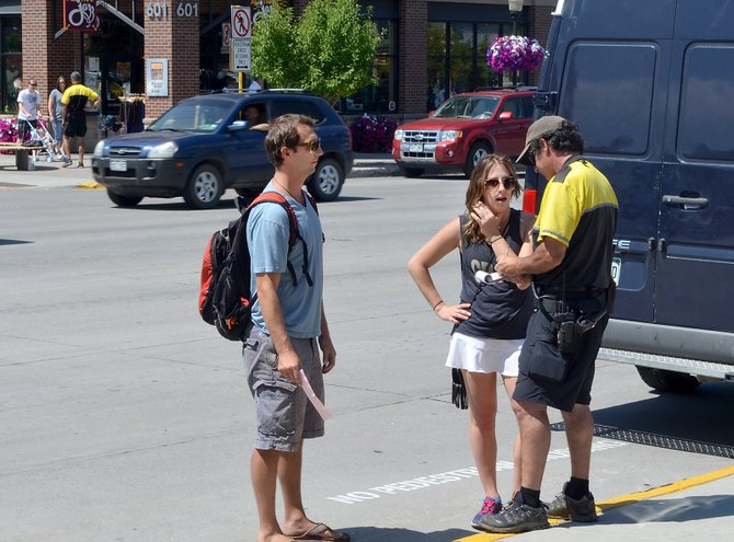 Steamboat Springs Police Department community service officer Scott Shaffer issues warnings for jaywalking to Adam Knapp and Dana Stein, both of Steamboat Springs, at the corner of Lincoln Avenue and Sixth Street on Aug. 17.