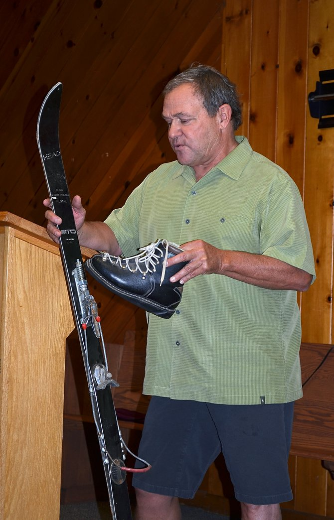 Ski Haus owner Rod Schrage demonstrates the binding system on a pair of original Ski Haus rental skis Friday during a Tread of Pioneers Museum brown bag lunch talk at the United Methodist Church of Steamboat Springs.