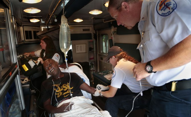 Denver Health paramedics Marsha Davis, back left, and Erin Cronin, center right, treat Tony Davis on Aug. 22 in an ambulance in downtown Denver. Paramedics in Denver respond to about 100,000 calls per year. Medical responders in isolated and less-populated rural and mountainous areas may answer a small fraction of that number. A patchwork emergency medical system has emerged with a wide disparity between the on-the-ground care you could expect along a rural highway and what you would see along the urbanized Front Range.