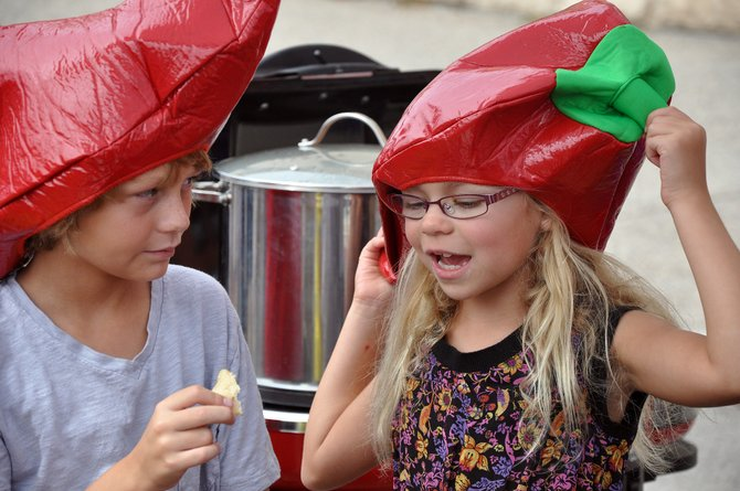 Katie Cannon, right, adjusts her chili pepper hat Sunday as she hangs out with Bodhi Bolton at the Chuck Wagon Chili Challenge in downtown Steamboat Springs.