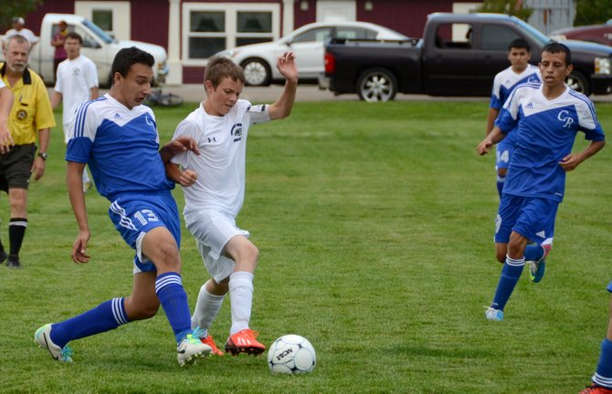 Tanner Snyder (in white) battles for possession of the ball during Moffat County's home game against Coal Ridge at Woodbury Sports Complex Tuesday. Moffat County lost the game 4-0 and is 0-1 this season.