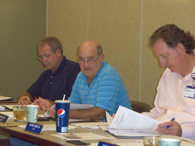 The Memorial Hospital board members, from left, Todd Jourgensen, Don Cook, and TMH Chief Executive Officer Chris Smolik look over paperwork at the monthly meeting Thursday night. Among other discussion points was the approval of a site lease to build and operate an outpatient dialysis center on the property.