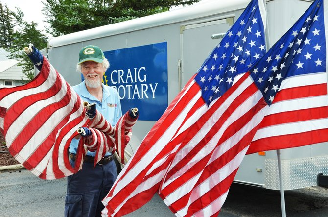 Craig Rotarian Randy Looper handles a group of American flags that will line Victory Way and Yampa Avenue on Wednesday in remembrance of the tragic terrorist attack that took place in New York City on Sept. 11, 2001.