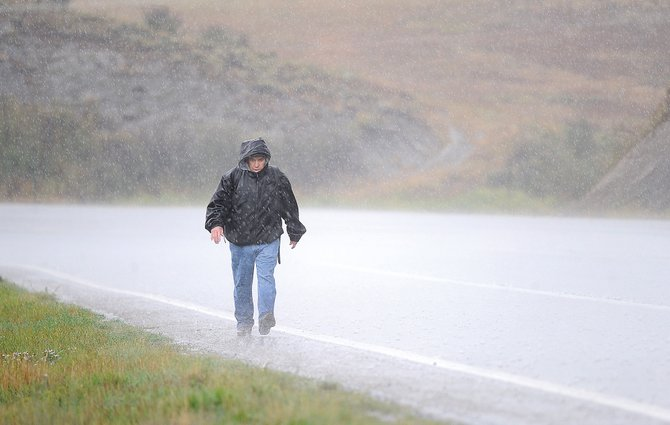 Steamboat Springs resident Andy Morris walks along U.S. Highway 40 on Tuesday afternoon during a steady downpour. Morris was hoping to catch the bus on his way to downtown Steamboat Springs.