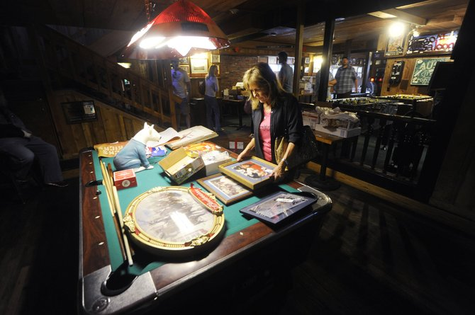 Steamboat Springs resident Chris Gallion looks at old photos Wednesday during an auction of all the contents inside The Tugboat Grill & Pub.