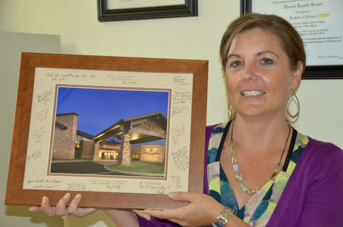 Tinneal Gerber holds up a commemorative photo of The Memorial Hospital signed by TMH board members and staff. Gerber recently resigned from the TMH board of trustees in order to better focus on her job with the Moffat County School District. Following her resignation, the Moffat County Commission is seeking a replacement for her seat on the board and is accepting applications through Oct. 1.