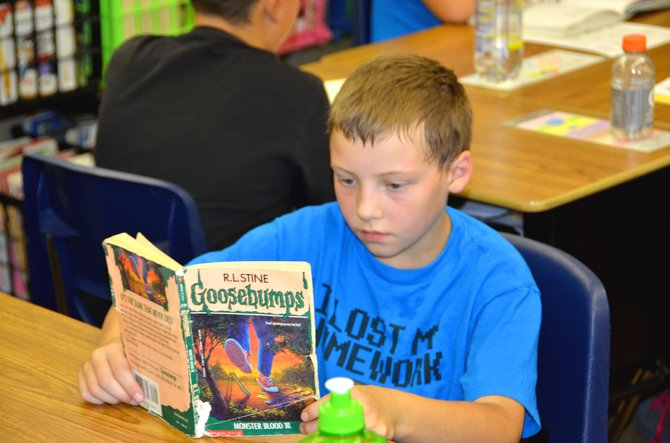 "Fourth-grader Matthew Jessen reads an R.L. Stine ""Goosebumps"" book Wednesday afternoon in Ty Kuberry's class at Sandrock Elementary School. Fourth- and fifth-graders from across the school district are involved in the Passport to Reading program, which encourages reading books from a variety of genres."