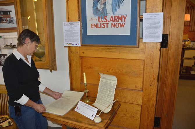 Debbie McLain, corresponding secretary for the Augusta Wallihan Chapter of the National Society of Daughters of the American Revolution, thumbs through a copy of the US Constitution on display at Museum of Northwest Colorado in Craig. DAR will be supporting Constitution Day and Constitution Week activities starting Tuesday.