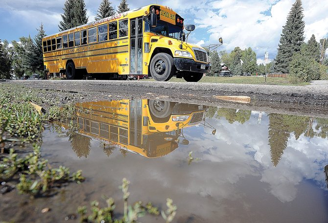 A Steamboat Springs school bus rolls past a puddle that has formed on Oak Street in downtown. Steamboat has received 3.05 inches of rain in the past seven days — more precipitation than was recorded here in June, July and August combined.