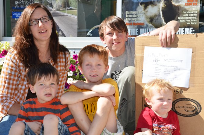 Caroline Dotson sits outside the Craig Daily Press office with her children, from left, Chandler, 3, Colton, 7, Caleb, 11, and Creed, 1, before dropping off a box for donations to help children and families affected by recent flooding in Colorado. Caleb and Colton came up with the idea to start the Hope Floats fundraiser to help those devastated by the floods.