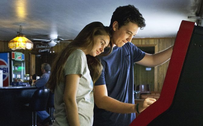 "Teens Sutter and Aimee (Miles Teller, Shailene Woodley) select a song from a jukebox in a highway bar in ""The Spectacular Now."" The movie is about the tumultuous life of a high school senior whose drinking habits seriously affect his relationships."