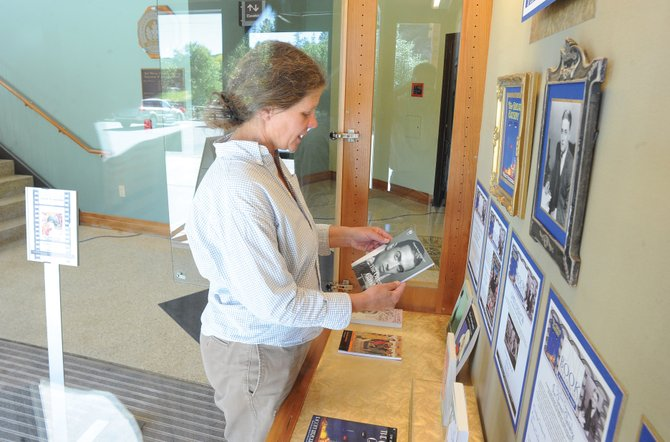 "Museum employee Karen Fitzgerald looks at a copy of ""The Great Gatsby"" while setting up a display inside Bud Werner Memorial Library. The F. Scott Fitzgerald book will be featured in a number of events this month as part of One Book Steamboat, which begins Saturday."