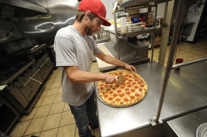 Blue Sage Pizza co-owner Michael Eller cuts a pizza Friday at the pizzeria's new location in Riverside Plaza. The business's Central Park Plaza location is moving to Wildhorse Marketplace.