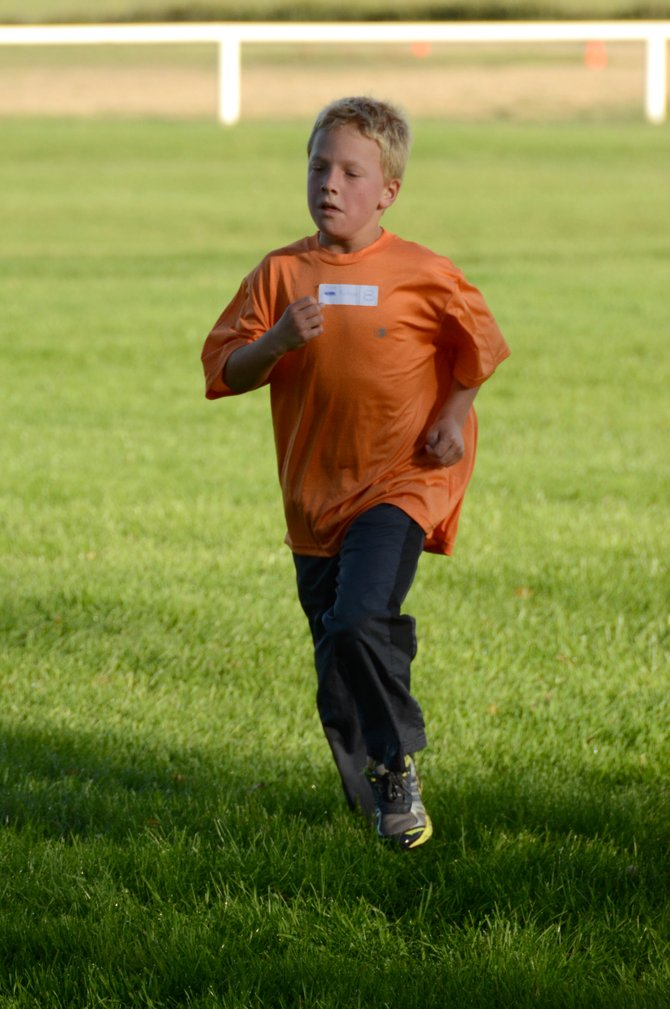 Noah Mortenson runs down the finishing stretch of the Leaf Cruncher 5K on Saturday at Loudy-Simpson Park. Mortenson was the top finisher in the boys 13-and-younger age group of the race.