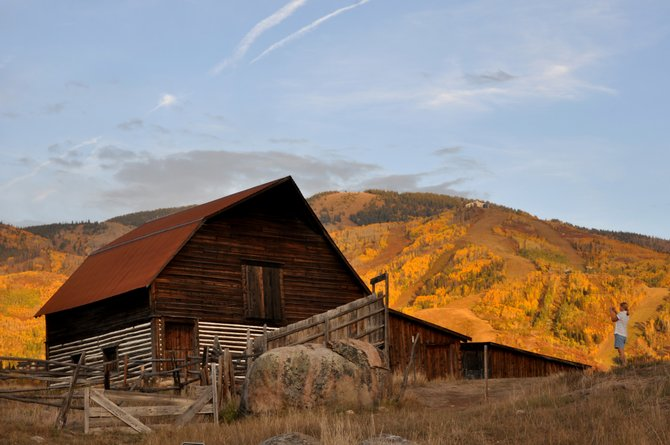 A person snaps a photo of the More Barn with a golden Mount Werner as a backdrop. The iconic Steamboat barn presents just one of many great photo opportunities in Routt County during autumn.