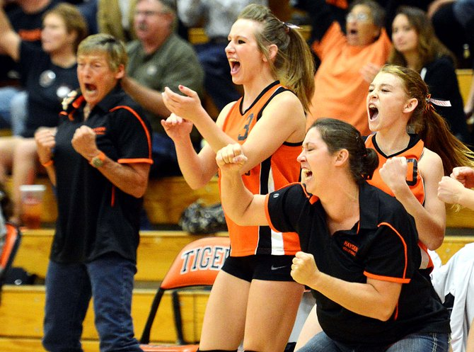 Hayden coach Christene Planansky leads the Tigers' bench in celebration after a point late in Saturday's match against Rangely. Hayden swept the Panthers in three sets.