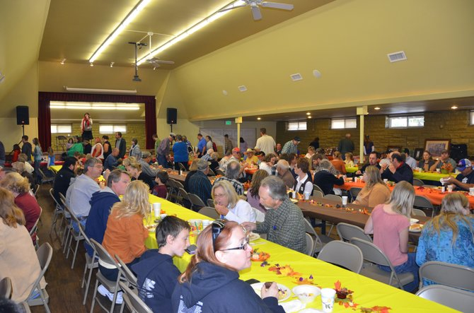 Craig residents gather together at the Moffat County Fairgrounds Pavilion Sunday afternoon for Love INC's seventh annual pig roast and silent auction fundraiser. Executive Director Pat Jones said she hoped to raise about $6,000 or more with the event.