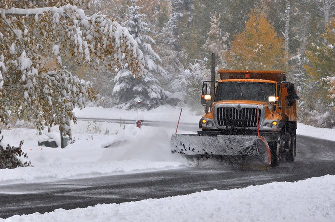 A city snowplow clears heavy snow off of Aspen Wood Lane early Friday morning.