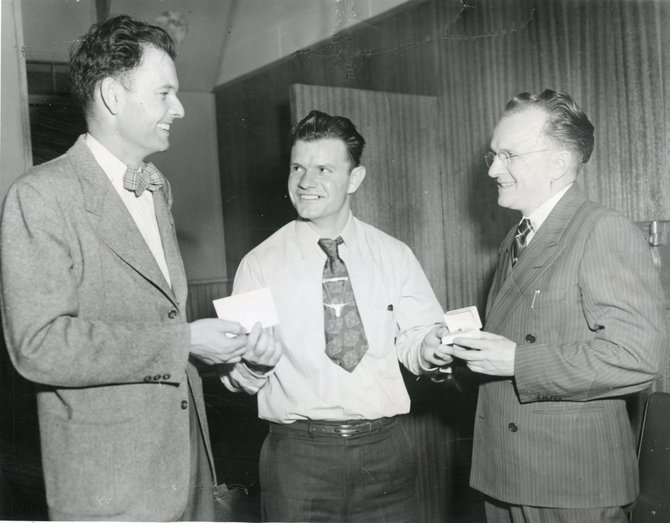 Vern Davis, center, receives his trip voucher from Merf Evans left, and a diamond ring from Howard Sather, right, after winning an all-expenses-paid trip to Hollywood in 1951 that included a television screen test.