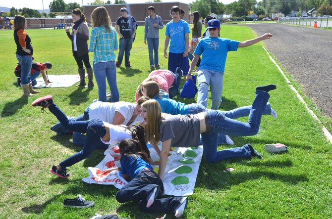 Moffat County High School students play bilingual Twister with the second and third-grade students of Sandrock Elementary's English Language Learner program. The day's events helped the MCHS students increase their skills speaking Spanish and also helped the Sandrock students feel more comfortable speaking English.
