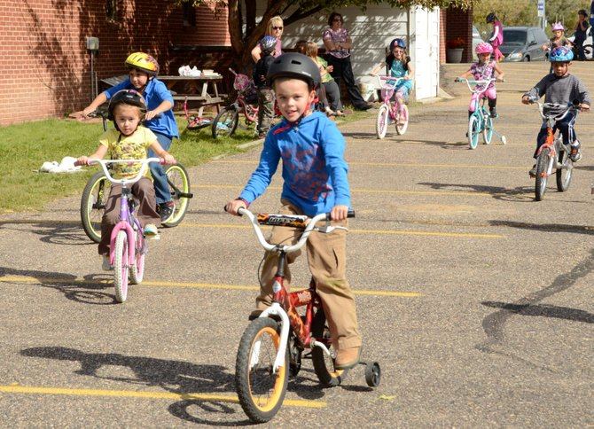 Jesse Vannoy, 6, leads a pack of kindergarten and first-grade bike riders into the turn Tuesday at Calvary Baptist School in Craig. Vannoy and 27 others participated in the school's Bike-a-Thon fundraiser, raising $2,000 with their efforts.