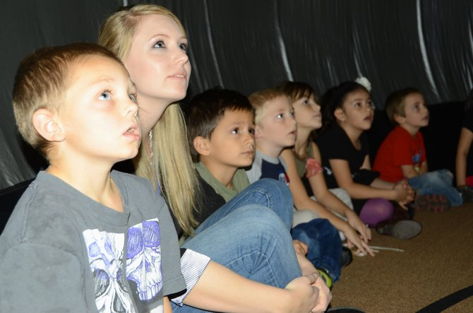 East Elementary School first-grade teacher Alisha Brown and her students gaze at the ceiling within the Sky Dome Planetarium Thursday afternoon. The Sky Dome is an educational presentation that will be available at Moffat County schools this week and open to the public Monday night at the Boys & Girls Club of Craig.