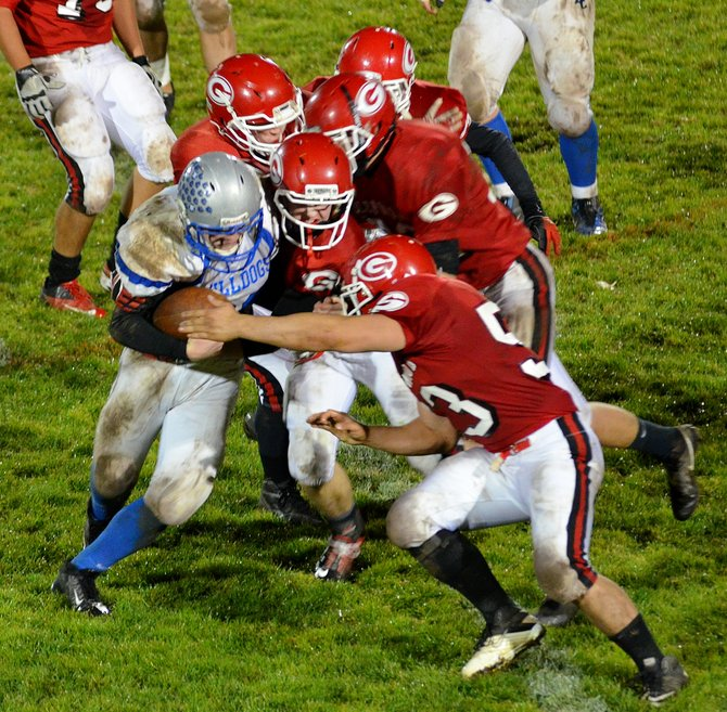 Moffat County running back Brett Lloyd is swarmed by four Glenwood Springs defenders in the second half of Friday's game in Glenwood Springs. The Demons beat the Bulldogs, 42-6.