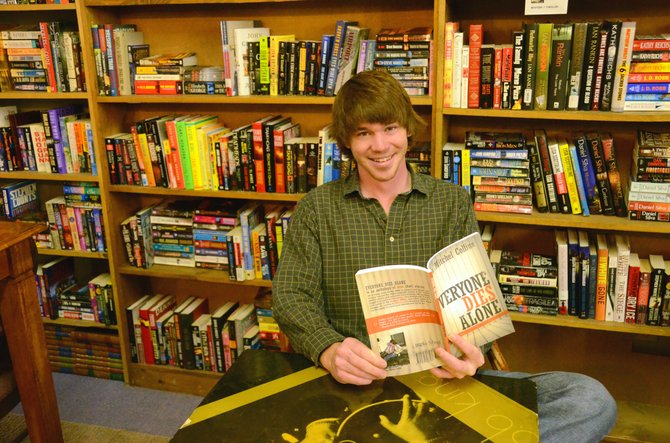 "Ryan Mitchel Collins sits down at one of the reading tables of Downtown Books with a copy of his work, ""Everyone Dies Alone."" Collins, a former Craig resident, will be signing copies Tuesday afternoon at the store."
